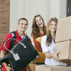 Three univertiy students in front of dormitory entrance, moving boxes into a college dorm room or apartment. Moving house is a teenager fall campus activity of action, happiness, and excitement of new roommates and homes. Friends, siblings, young men and women help each other relocate, working together to carry luggage.