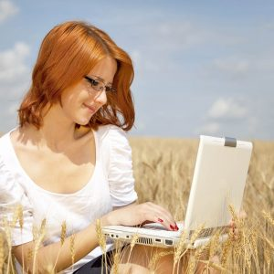 Young Businesswomen in white working with notebook at wheat field.