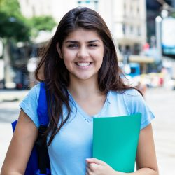 Portrait of young mexican female student in the city in the summer